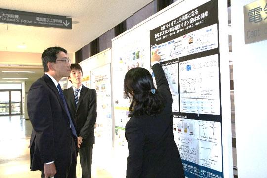 ポスター展示で研究内容の紹介を聞く北山高等教育局専門教育課長(写真左)